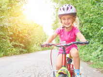 Happy child riding a bike in outdoor. Royalty Free Stock Images