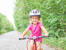 Happy child riding a bike in outdoor. Royalty Free Stock Photo