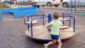Happy child riding on the carousel. A boy is playing on the playground. stock footage