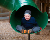 Happy child riding down slide Royalty Free Stock Photography