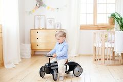 Happy child riding toy vintage car. Funny kid playing at home. Summer vacation and travel concept. Active little boy driving a car royalty free stock photo