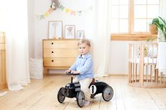 Happy child riding toy vintage car. Funny kid playing at home. Summer vacation and travel concept. Active little boy driving a car. Pedal in the nursery royalty free stock photo