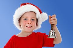 Happy child ringing bell on blue. Cute boy ringing hand bell in front of him, blue background Royalty Free Stock Image