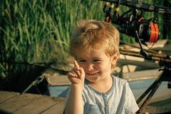 Happy child with rod on fishing pier stock photos