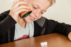 Happy child rolling dice on table Royalty Free Stock Photos