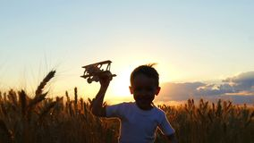 A happy child is running across a wheat field during sunset, holding a toy plane. The boy shows the flight of the