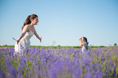 Happy child running into the arms of smiling mother on the flower field. In summer day Stock Photography