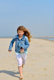 Happy child running on the beach Stock Photos