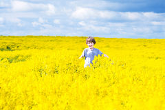 Happy child running in a field of yellow flowers. Happy laughing child running in a field of yellow flowers Royalty Free Stock Images