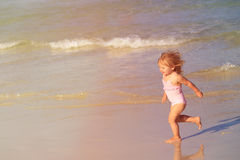 Happy child running and jumping in the waves at beach Stock Image