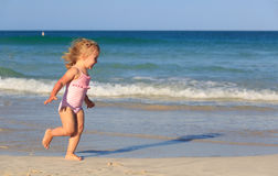 Happy child running and jumping in the waves at beach Royalty Free Stock Image