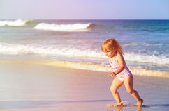 Happy child running and jumping in the waves at beach Stock Photo