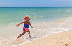 Happy child running and jumping in the waves at beach Stock Photos
