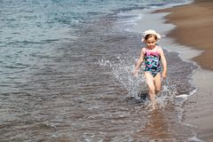 Happy child running and jumping in the waves royalty free stock image