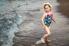 Happy child running and jumping in the waves stock image