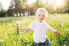 Happy child running on meadow of flowers. Happy little boy running on meadow of flowers with bouquet of wild daisies. Cute smiling child at camomile field at Royalty Free Stock Images