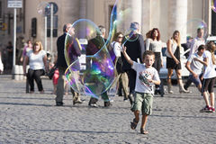 Happy child running towards a soap bubble Royalty Free Stock Images
