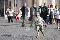 Happy child running towards a soap bubble Stock Images