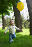 Happy child running with a yellow balloon Stock Photos