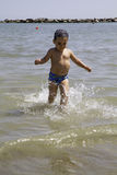 Happy child runs into sea to swim, vacation in Italy Stock Images