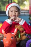 Happy child in santa hat with a gift near the Christmas tree, Ch Stock Image