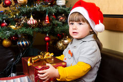 Happy child in Santa hat opening Christmas gift box Stock Images