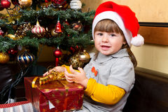 Happy child in Santa hat opening Christmas gift box Royalty Free Stock Photography