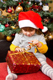 Happy child in Santa hat opening Christmas gift box Royalty Free Stock Images