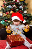 Happy child in Santa hat opening Christmas gift box Stock Photos