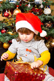 Happy child in Santa hat opening Christmas gift box Royalty Free Stock Image