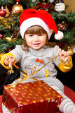 Happy child in Santa hat opening Christmas gift box Stock Photo