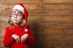Happy child in santa hat shows ok sign on a wooden background, c. Opy space. Christmas background Royalty Free Stock Images