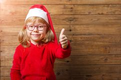Happy child in santa hat shows ok sign on a wooden background, c. Opy space. Christmas background Stock Images