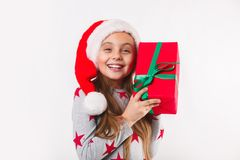 Happy child in Santa red hat holding Christmas presents. royalty free stock image
