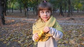 Happy child in scarf blowing soap bubbles having fun into camera outdoors at park. Happy child in a scarf blowing soap bubbles having fun into camera outdoors at stock video