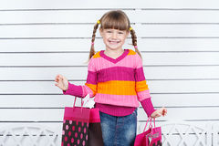 Happy child with shopping bags. She is enjoying the gifts and holidays Stock Photo