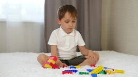 A happy child sits on a bed in a room and builds from coloured blocks, playing and imagining. The concept of construction stock video
