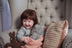 The happy child sits in a chair. Happy laughter of the red-haired baby. The happy child sits in a chair. The girl with red hair laughs. Happy laughter stock photos
