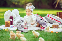 Happy child sits on a meadow around easter decoration stock images