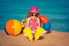 Happy child sitting on the beach Stock Photo