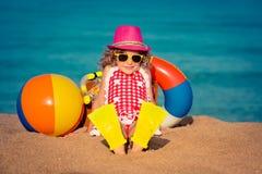 Happy child sitting on the beach Stock Photo
