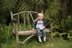 A happy child sitting on a garden bench Stock Photography