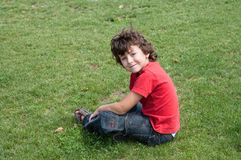 Happy child sitting on the grass Royalty Free Stock Photos