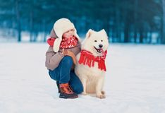 Happy child sitting with his white Samoyed dog in winter day royalty free stock images