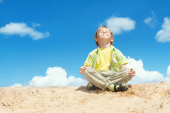 Happy Child Positive Think, Boy Sitting in Yoga Lotus position over blue sky on the top. Kid Happiness concept. stock photos