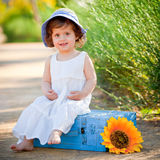 Happy child sitting outdoors in summer Stock Photo