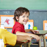 Happy child sitting in school. Happy abecedarian child sitting smiling in elementary school classroom royalty free stock photos