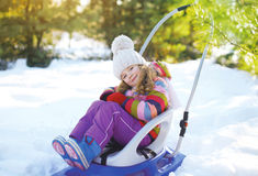Happy child sitting in the sled Stock Image