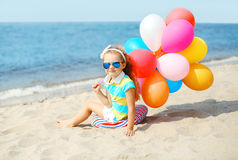 Happy child sitting on summer beach with colorful balloons Royalty Free Stock Images