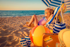 Happy child sitting on the sunbed Stock Photography